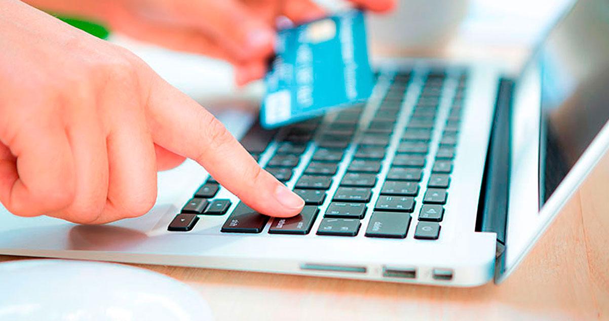 Persona realizando un compra en línea con una tarjeta crédito en su mano