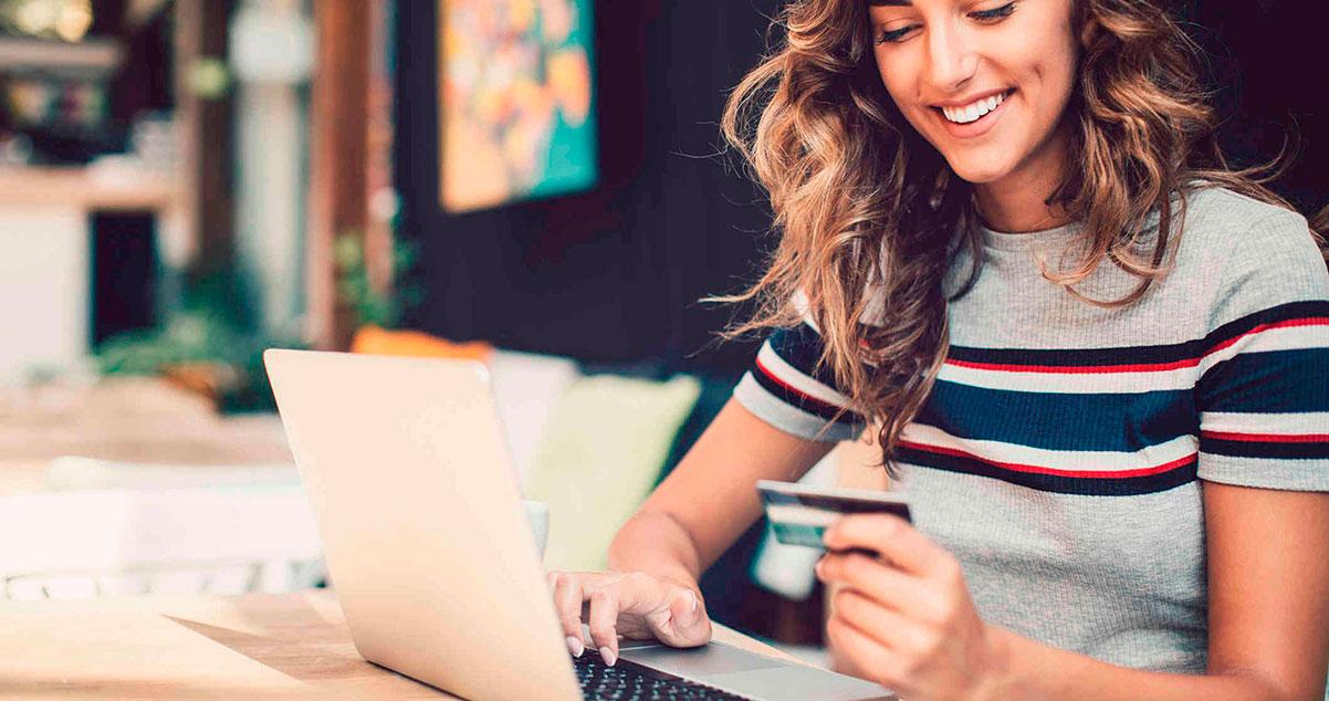Mujer sonriente realizando una compra en línea desde su portátil