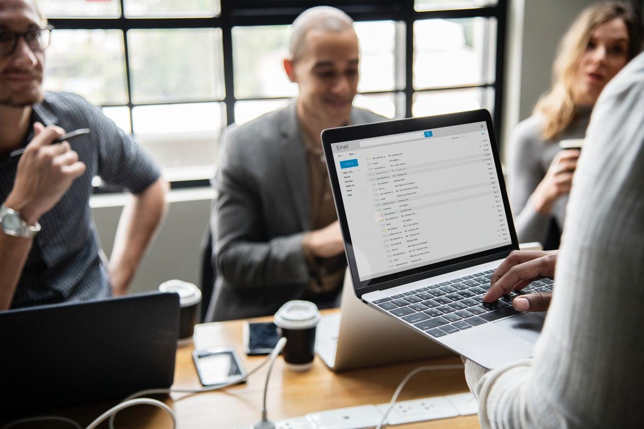 Equipo de trabajo con 4 personas reunidas alrededor de un portátil que muestra una plataforma de email-marketing
