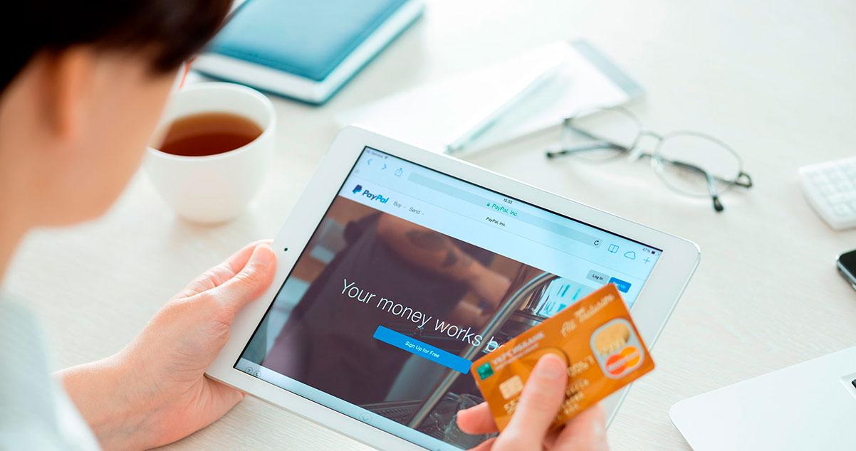 Hombre navegando un comercio electrónico con una tarjeta de crédito en la mano