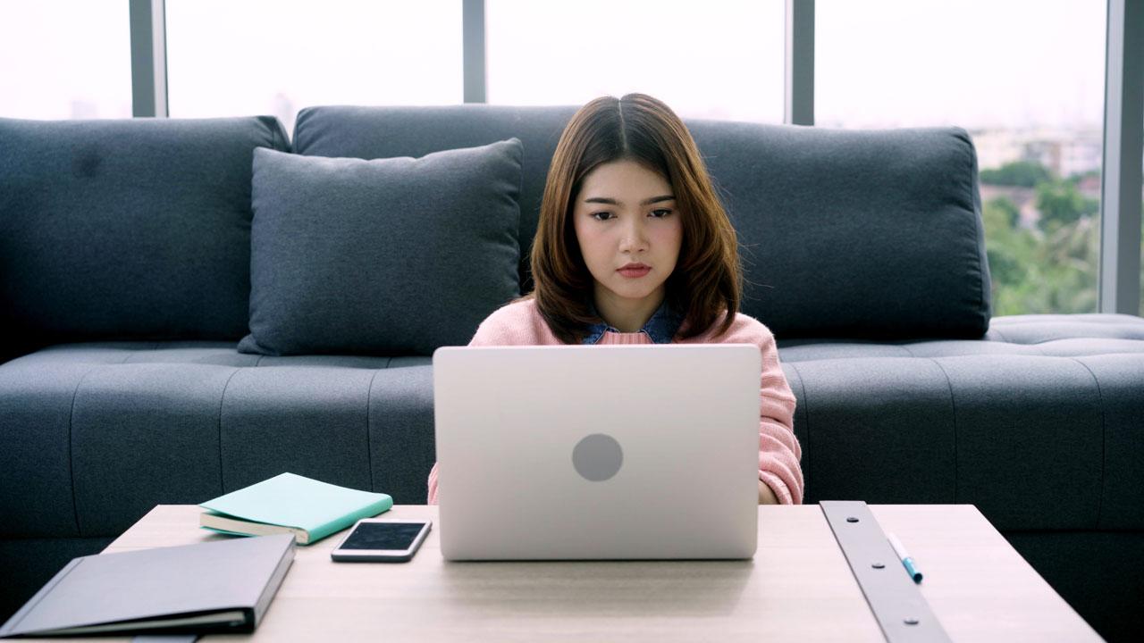 Mujer frente a un computador realizando una compra online con cara de preocupación