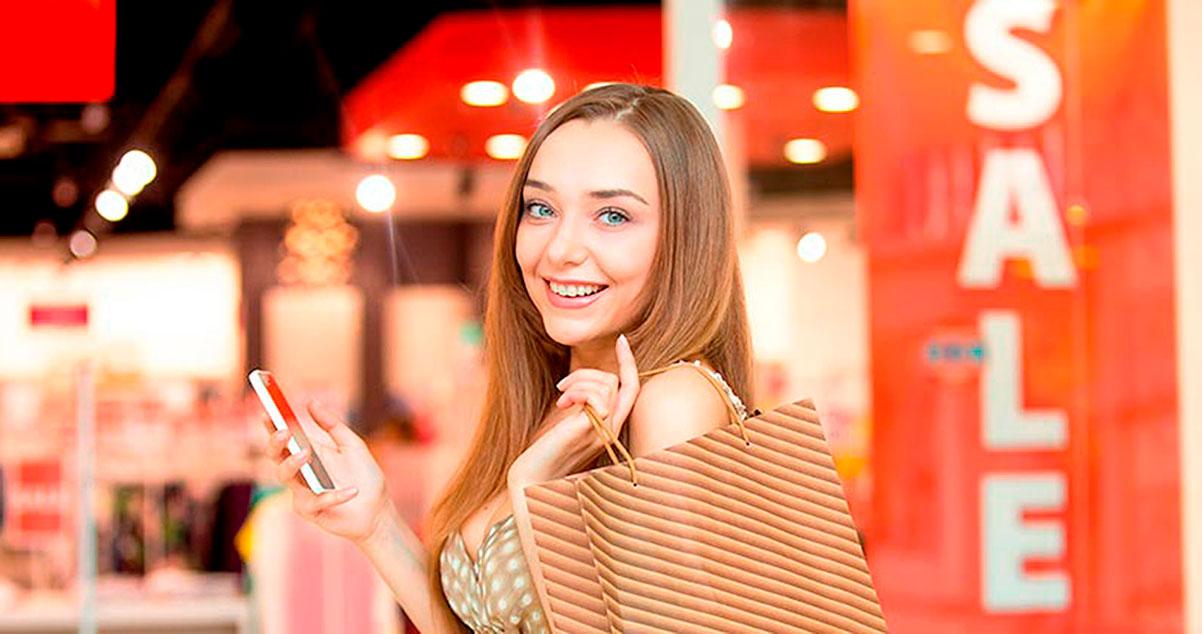 Mujer sonriente con una bolsa de compras y sosteniendo un celular