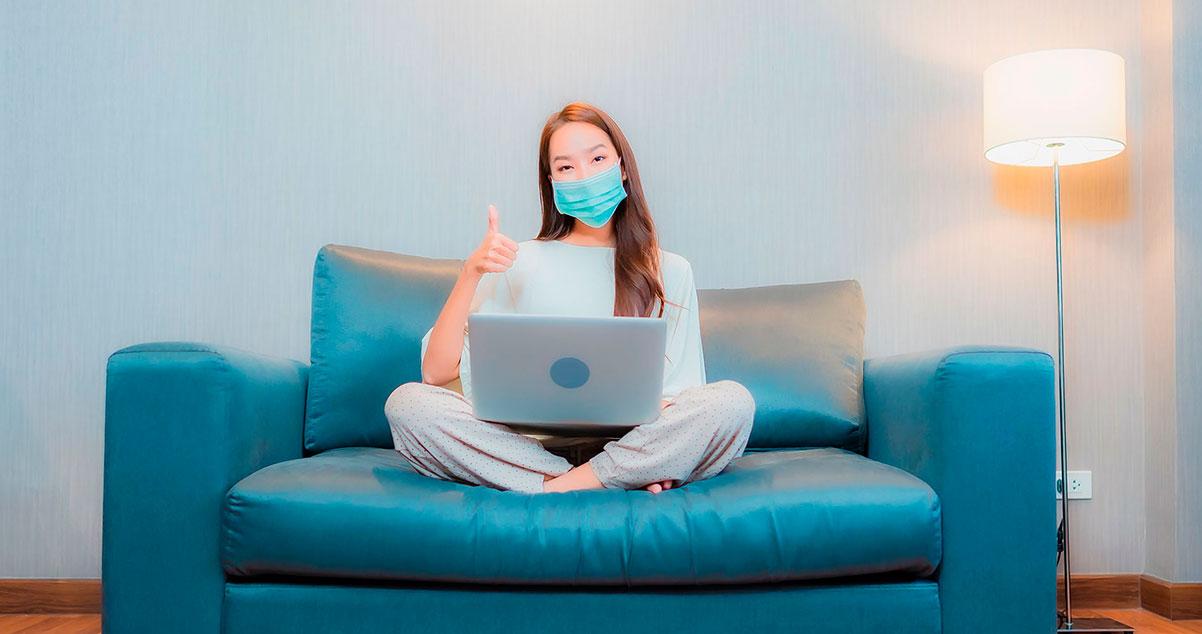 Fotografía de una chica con tapabocas sentada en un sofa con un portatil haciendo señal de aprobación con el pulgar
