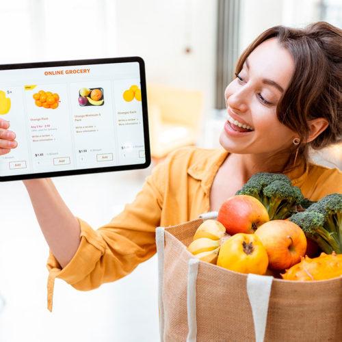 Mujer con un paquete de frutas adquirido a traves de una tablet, representa el mobile commerce como tendencia en crecimiento citado en este artículo de webkreativo