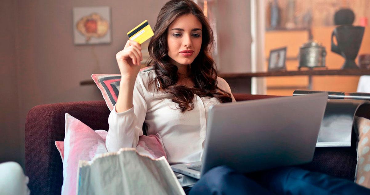 Mujer sentada en sofá sosteniendo una tarjeta de crédito en su mano realizando una compra en línea desde su portátil