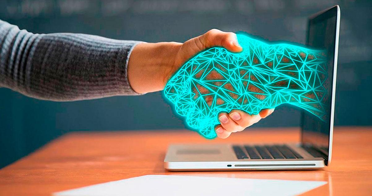 Una mano humana estrechando la mano de un robot a través de una pantalla de computador - WebKreativo